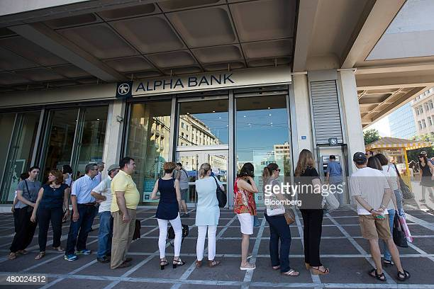 A long queue of customers wait to withdraw cash from an automated teller machine outside an Alpha Bank AE bank branch in Athens Greece on Thursday...