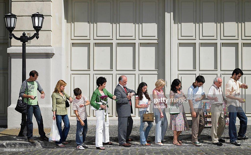 Long queue of people in street, side view