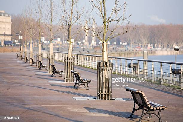 Long shadows from early morning winter sunrise on Bordeaux promenade