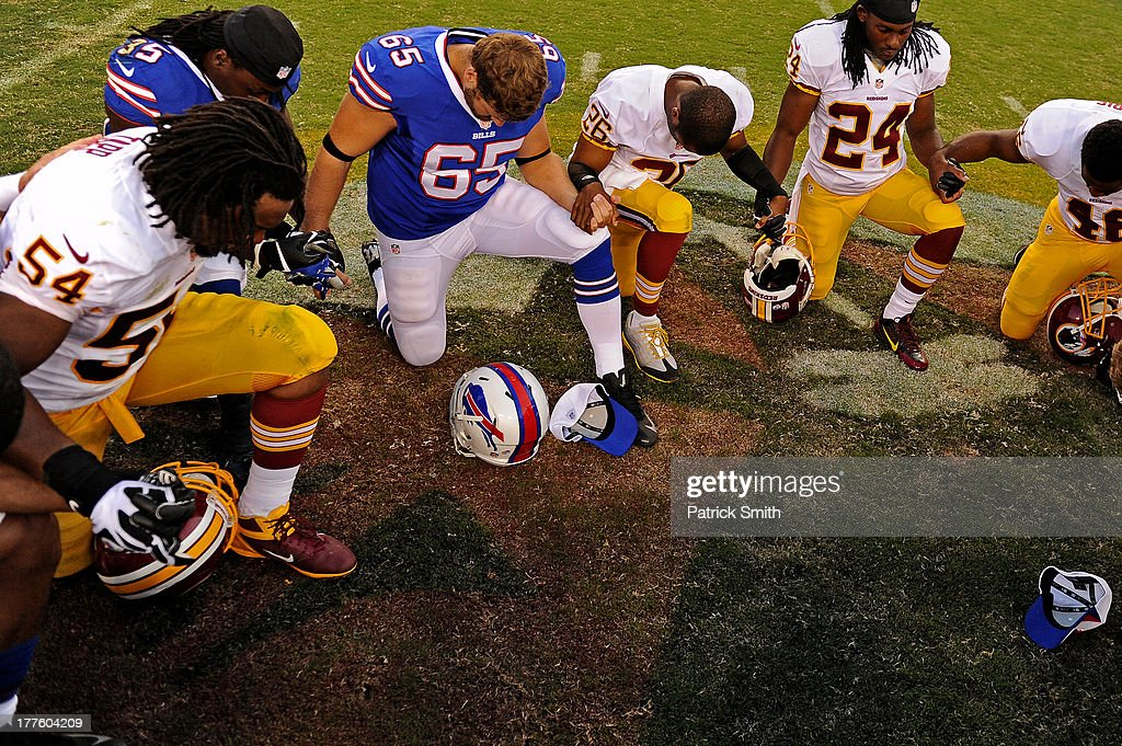 Long snapper Garrison Sanborn #65 of the Buffalo Bills, safety DeJon Gomes #24 of the Washington Redskins and other players pray after an NFL preseason game at FedExField on August 24, 2013 in Landover, Maryland. The Washington Redskins won, 30-7.