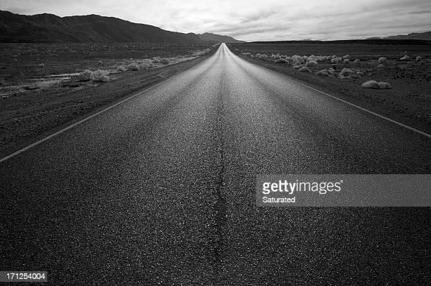 Longue route tout droit en noir et blanc