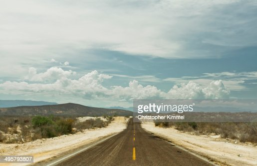 A long straight road leading through the Mexican Baja landscape