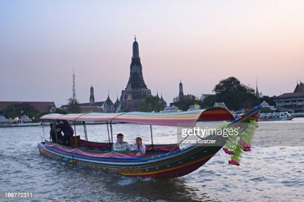 A long tail boat glides up the Chao Phraya River with Wat Arun in the background Wat Arun is located on the west bank of the river and can be reached...