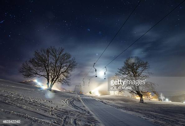 A long time exposed picture shows a ski lift as snowmakers blow artificial snow on a tourist course on the eve of the men's night slalom of the FIS...