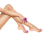 Healthy female Legs. Spa. Long woman legs and orchids isolated on white background. Skin care. Depilation. Epilation