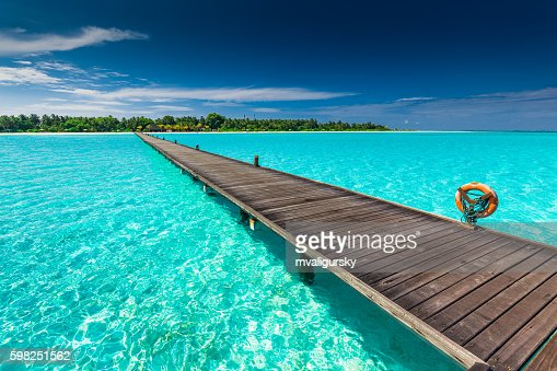 Long wooden jetty over atoll and tropical island in Maldives : Stock Photo