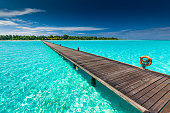 Long wooden jetty over atoll and a tropical resort island in Maldives