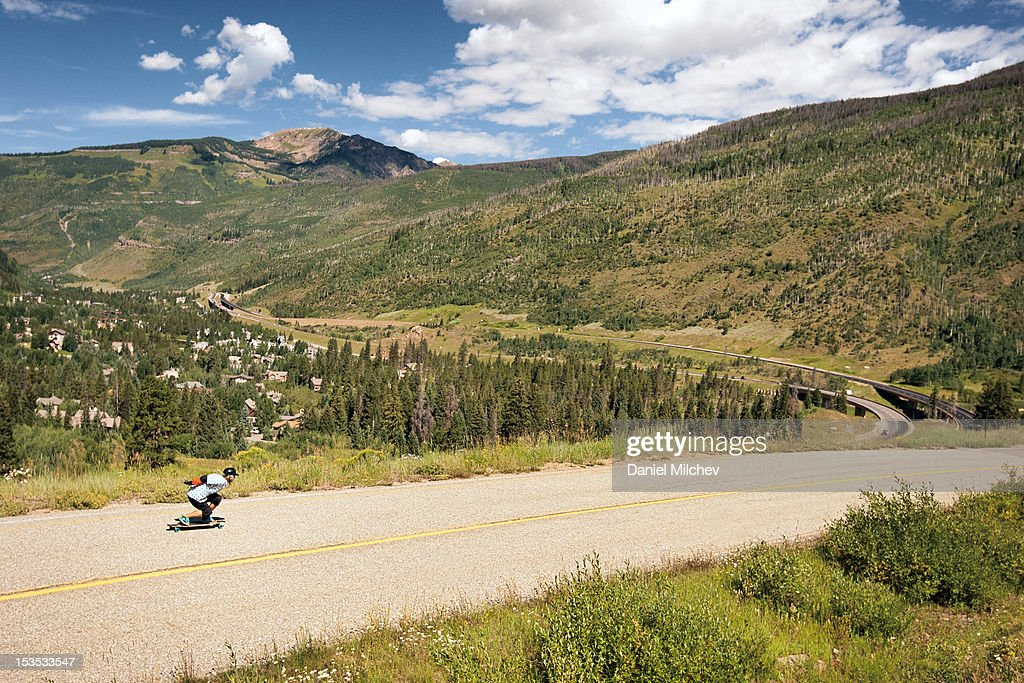 Longboarder skating on a scenic road. : Stock Photo