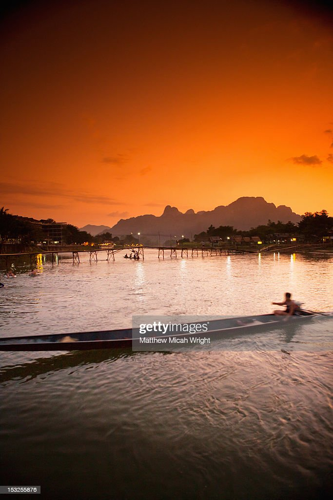 A longboat crossing the river at sunset.