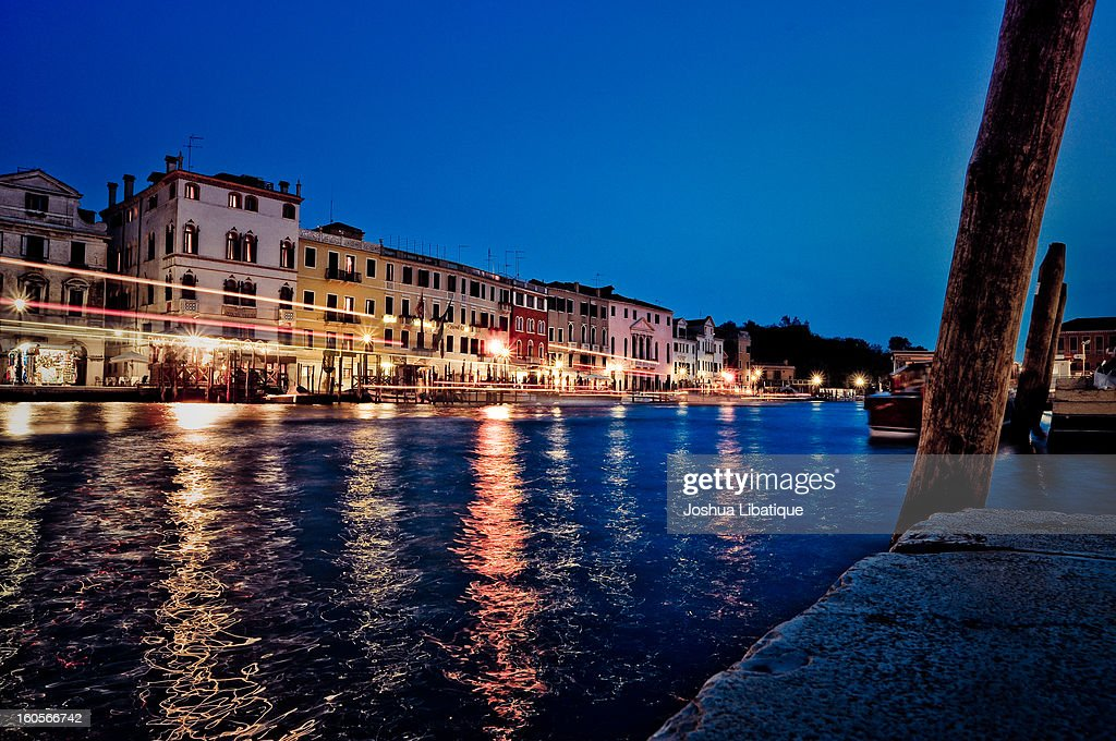 CONTENT] A long-exposure shot taken after sunset in Venice. Lights of passing boats can be seen streaking through the picture, and reflections of lights and storefronts are reflected in the water. Taken near Ponte Degli Scalzi Bridge.