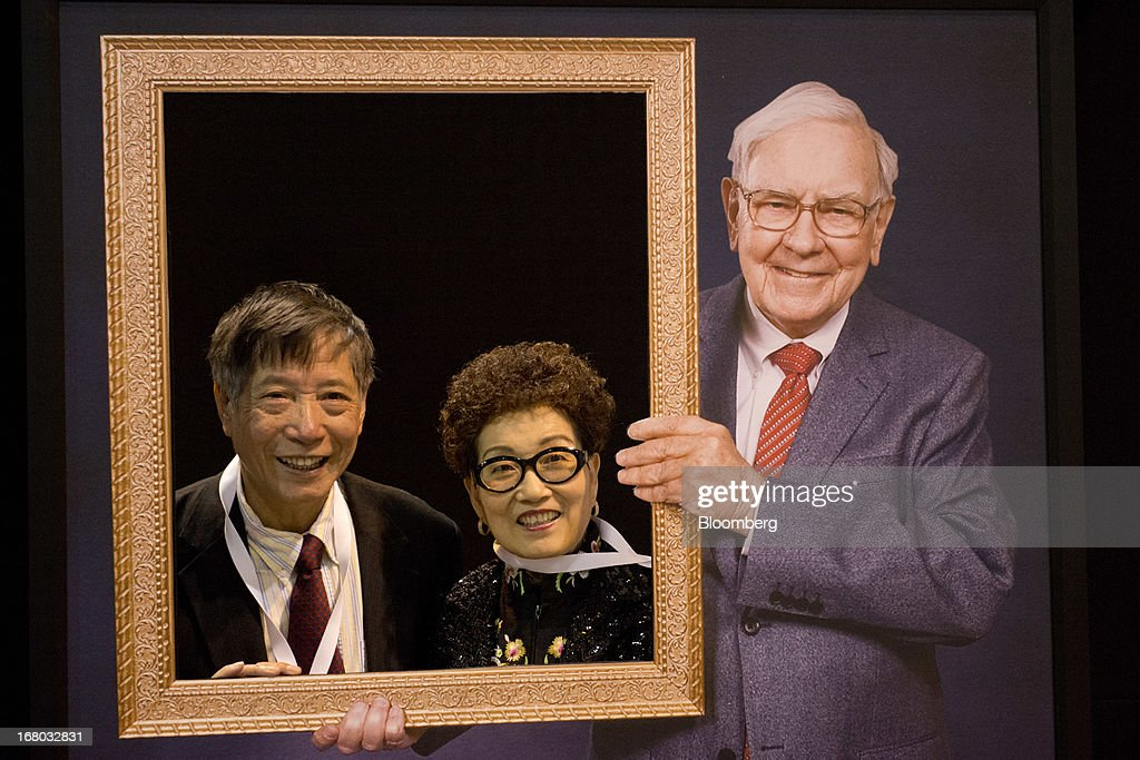 Longgen Zhang, left, and Yedi Wang stand for a photograph with an image of Warren Buffett, chairman and chief executive officer of Berkshire Hathaway Inc., on the exhibition floor during the Berkshire shareholders meeting in Omaha, Nebraska, U.S., on Saturday, May 4, 2013. Buffett's Berkshire Hathaway Inc.'s cash hoard hit a record as first-quarter profit jumped 51 percent on gains from equity-linked derivatives and insurance operations. Photographer: Daniel Acker/Bloomberg via Getty Images