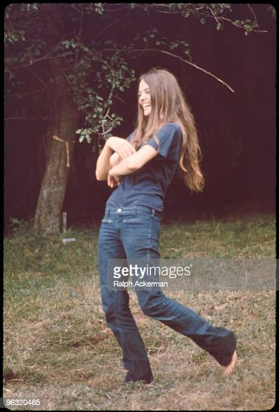 Longhaired barefoot laughing young woman at the Woodstock music festival August 1969