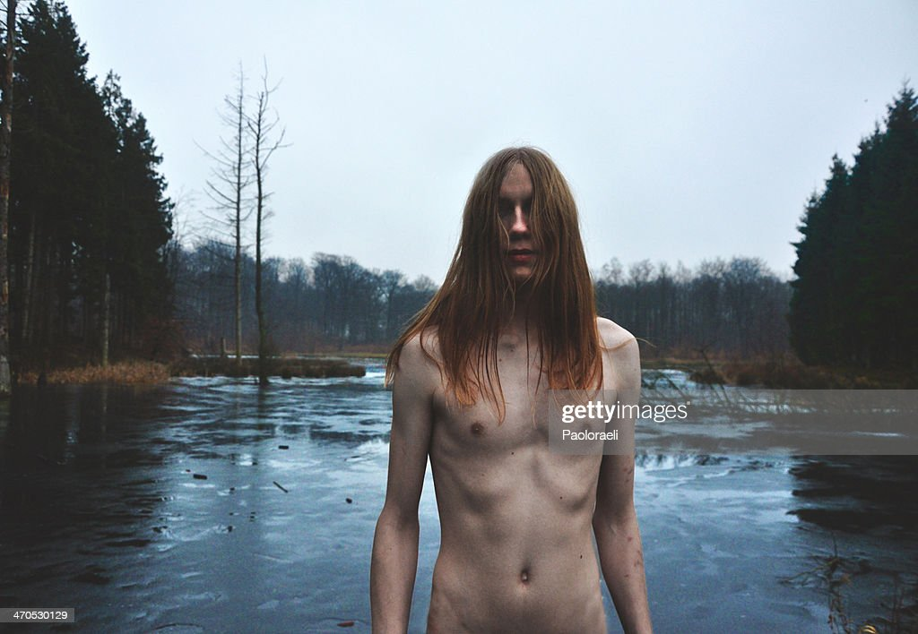 Long-haired boy in the swamp : Stock Photo