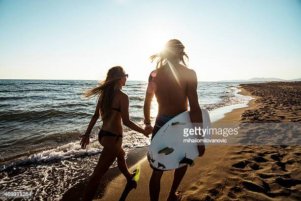 Long-haired couple with surfboard walking on the beach