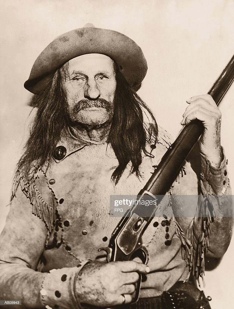 Long-haired man holding rifle, portrait (B&W sepia tone) : Stock Photo