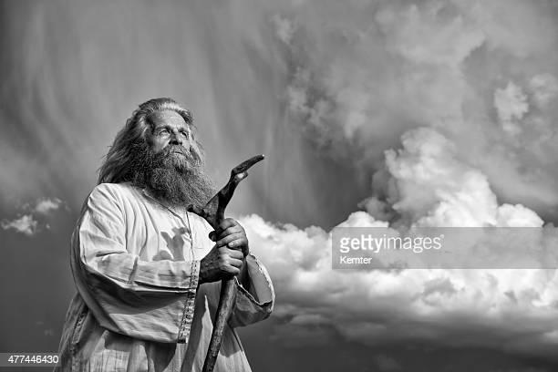 À poils longs, prophète debout en face de Ciel menaçant