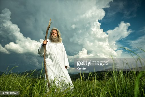 long-haired prophet standing in front of dramatic sky