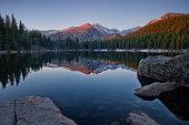 Longs Peak reflects in the still waters of bear Lake In Rocky Mountain national park