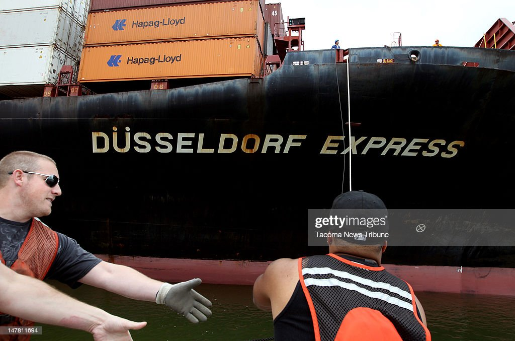 Longshoremen Luke Fuller and Robert Ross, from left, pull on line thrown down from the Dusseldorf Express immediately after it arrives in the Blair Waterway at the Port of Tacoma, July 2, 2012.