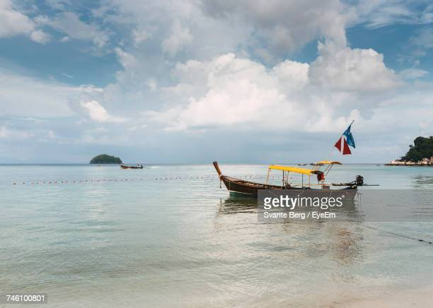 Longtail Boat Moored On Sea At Ko Lipe Against Sky
