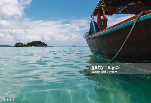 Longtail Boat On Sea Against Cloudy Sky