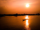 Longtail boat cross the river in sunset time. By mobile shooting.