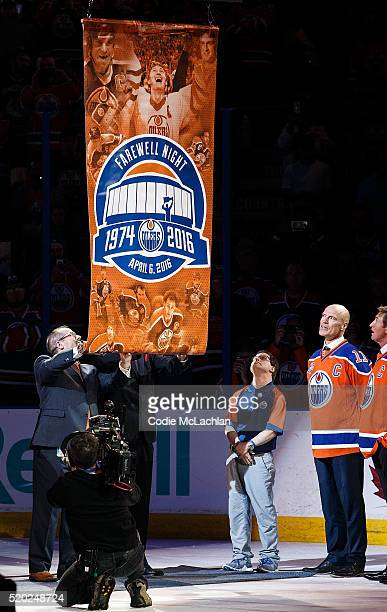 Longtime Oilers dressing room attendant Joey Moss along with former Oilers Mark Messier and Wayne Gretzky watch as a banner is lowered from the...