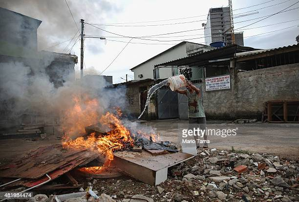 Longtime resident and holdout Nelson Raimundo da Silva douses a garbage fire in the Vila Autodromo 'favela' community with Olympic Park construction...