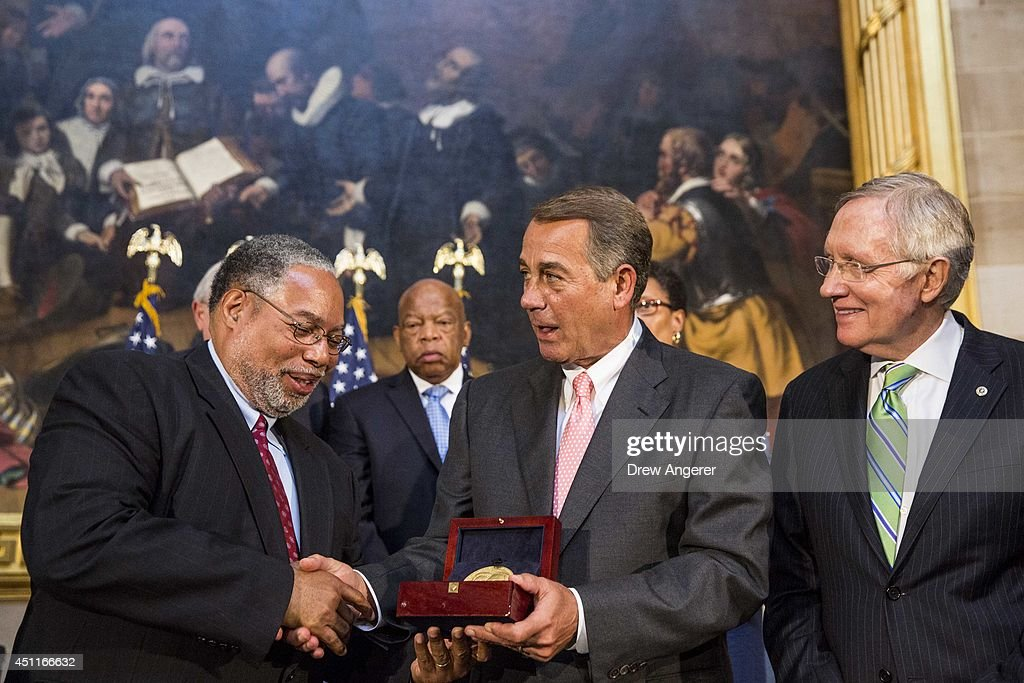 Lonnie Bunch (L), Founding Director of the Smithsonian National Museum of African American History and Culture, accepts the Congressional Gold Medal on behalf of Dr. Martin Luther King, Jr. and Coretta Scott King, from Speaker of the House John Boehner (R-OH) (C), on Capitol Hill, June 24, 2014 in Washington, DC. Senate Majority Leader Harry Reid (D-NV) looks on at right. The Congressional Gold Medal is Congress's highest civilian honor.