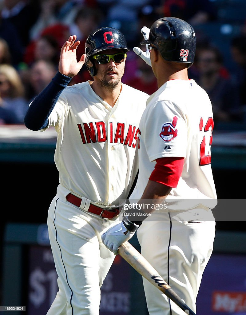 Lonnie Chisenhall of the Cleveland Indians celebrates with teammate Michael Brantley after scoring against the Chicago White Sox during the sixth...