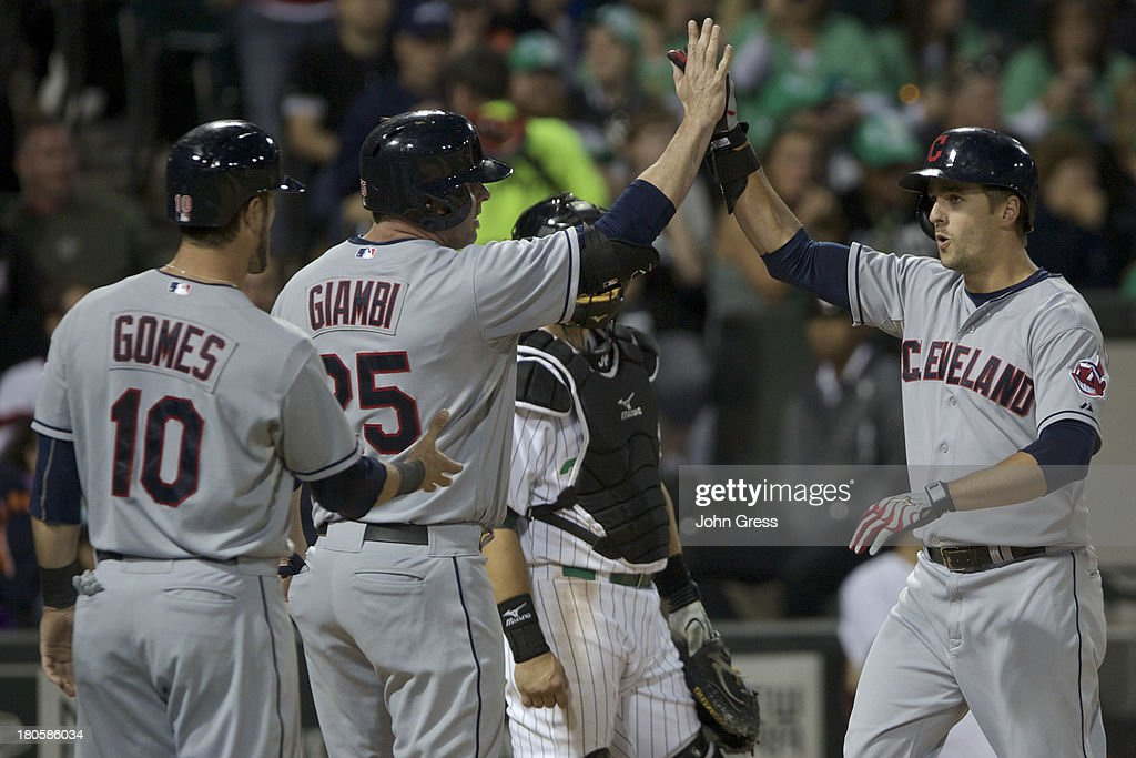 <a gi-track='captionPersonalityLinkClicked' href=/galleries/search?phrase=Lonnie+Chisenhall&family=editorial&specificpeople=6796448 ng-click='$event.stopPropagation()'>Lonnie Chisenhall</a> #8 of the Cleveland Indians celebrates with teammates <a gi-track='captionPersonalityLinkClicked' href=/galleries/search?phrase=Jason+Giambi&family=editorial&specificpeople=194953 ng-click='$event.stopPropagation()'>Jason Giambi</a> #25 and <a gi-track='captionPersonalityLinkClicked' href=/galleries/search?phrase=Yan+Gomes&family=editorial&specificpeople=9004037 ng-click='$event.stopPropagation()'>Yan Gomes</a> #10 after hitting a three-run home run against the Chicago White Sox during the fourth inning of their MLB game at U.S. Cellular Field on September 14, 2013 in Chicago, Illinois.