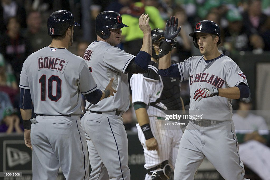 Lonnie Chisenhall #8 of the Cleveland Indians celebrates with teammates Jason Giambi #25 and Yan Gomes #10 after hitting a three-run home run against the Chicago White Sox during in the fourth inning of their MLB game at U.S. Cellular Field on September 14, 2013 in Chicago, Illinois.