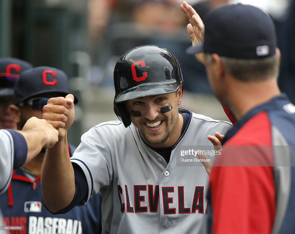 Lonnie Chisenhall of the Cleveland Indians is congratulated after scoring on a double by Nick Swisher during the fifth inning of game one of a...