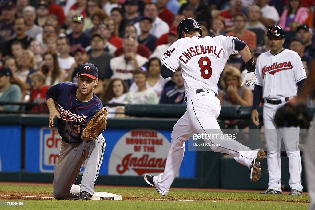 Lonnie Chisenhall #8 of the Cleveland Indians is out at first base as Justin Morneau #33 of the Minnesota Twins fields the throw during the fifth inning of their game on August 23, 2013 at Progressive Field in Cleveland, Ohio. The Twins defeated the Indians 5-1.