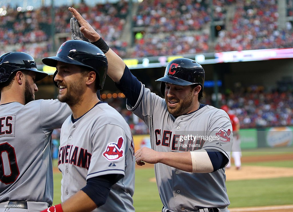 Lonnie Chisenhall of the Cleveland Indians raises his had and congratulated by is team mates for hitting a three run home run in the third inning...