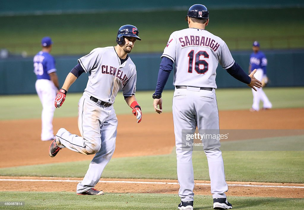 Lonnie Chisenhall of the Cleveland Indians rounds third base and is congratulated by third base coach Mike Sarbaugh after hitting a tworun home run...