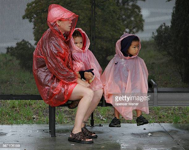 Lonnie Jones with her two kids Jackie and Robbie brighten the bench while waiting for the bus in Santa Monica as rain arrives in the southland Monday...