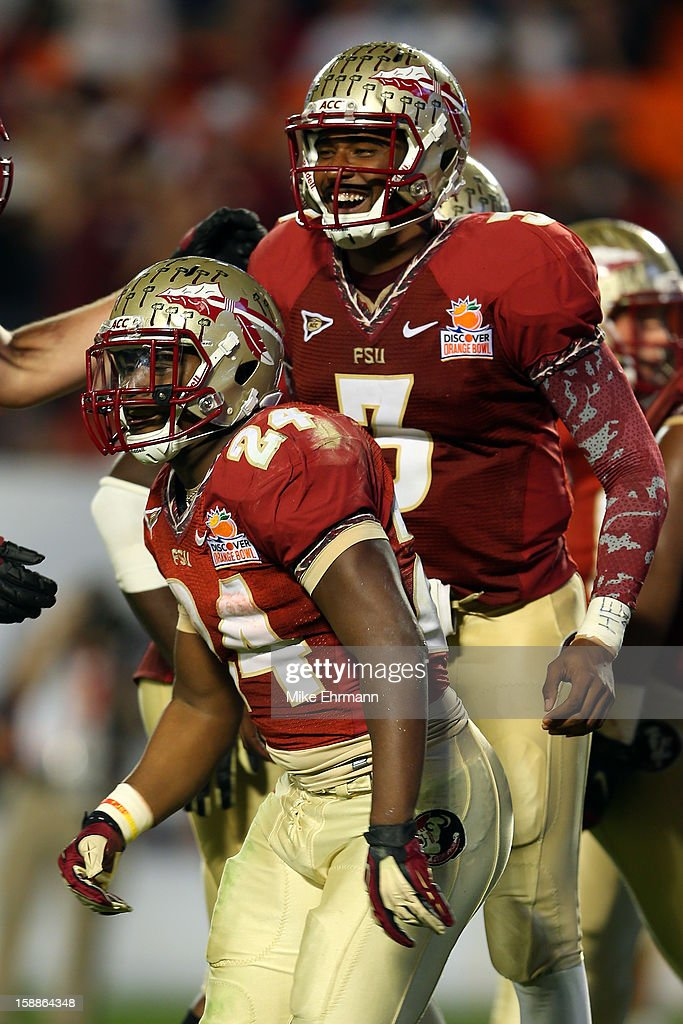 Lonnie Pryor #24 and EJ Manuel #3 of the Florida State Seminoles celebrate after Pryor scored a 37-yard rushing touchdown in the fourth quarter against the Northern Illinois Huskies during the Discover Orange Bowl at Sun Life Stadium on January 1, 2013 in Miami Gardens, Florida.