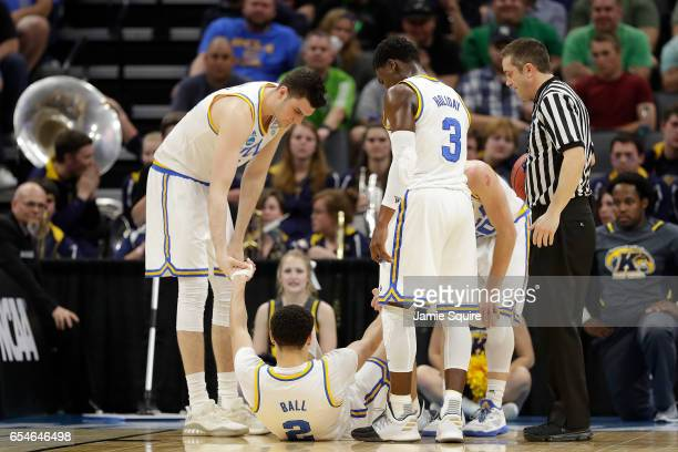 Lonzo Ball of the UCLA Bruins is helped up after falling to the court and sustaining an injury against the Kent State Golden Flashes during the first...