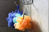 Light catches loofahs hanging from a rack.