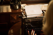 In front of her is a typewriter and empty paper, she is ready to write a new article for the new edition of the newspaper.