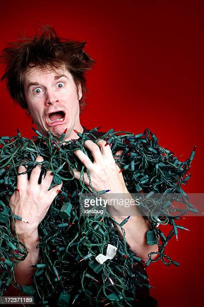 Look of Horror on Man with Tangled Christmas Lights