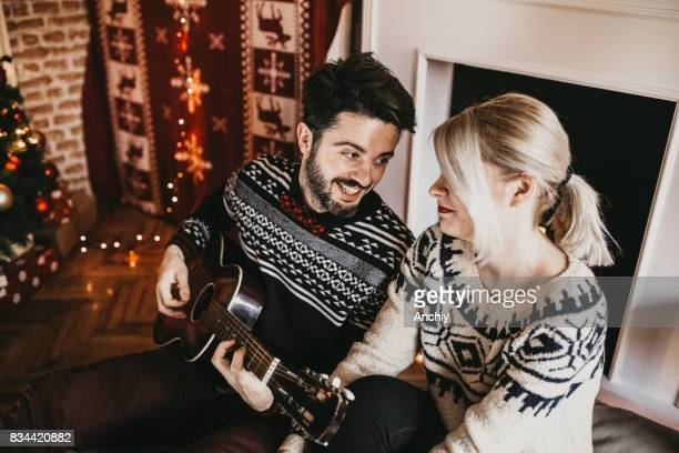 Look what I got. Husband playing guitar to his wife. Christmas time