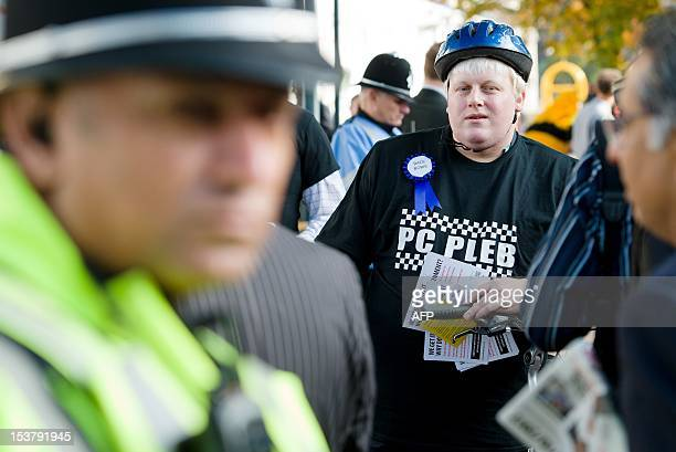 A lookalike of Mayor of London Boris Johnson hands out flyers protesting about proposed cuts in the police service on the third day of the annual...