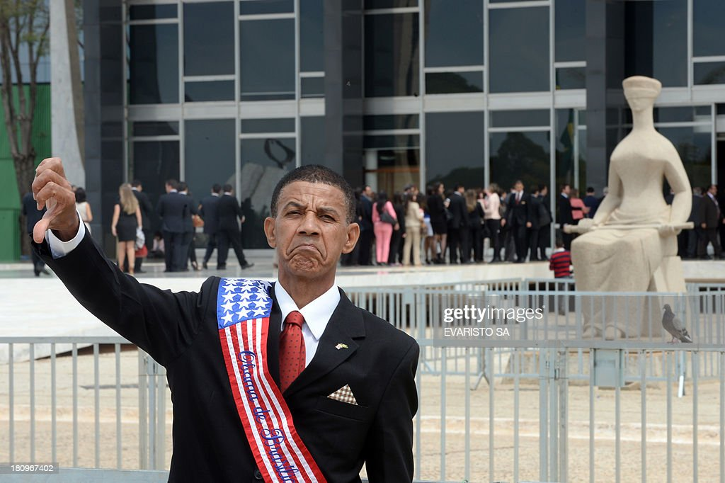 A look-alike US President Barack Obama poses in front of Supreme Court during a protest against the approval of the review of the appeals that will result in a new trial for 11 of the accused in the Mensalão scandal, in Brasilia on September 18, 2013. The session was held to review the appeals of those convicted for diverting at least $35 million in public money to bribe legislators to get their support for former President Luiz Inacio Lula da Silva's minority government after he took office in 2003. AFP PHOTO/Evaristo Sa