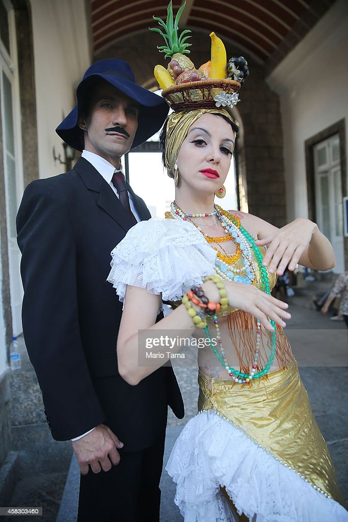 Lookalikes of famed aviator Alberto Santos-Dumont (L) and famed singer Carmen Miranda, both entombed in the cemetery, pose during Day of the Dead festivities at Sao Joao Batista cemetery on November 2, 2014 in Rio de Janeiro, Brazil. Brazilians often mark the traditional Mexican holiday by visiting loved ones' graves and occasionally leaving offerings of food or drink.