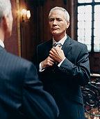 CEO Looking at a Mirror in a Pinstripe Suit Adjusting His Tie