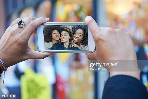 Looking at selfie of three friends.