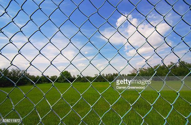 Looking At The Sky Through A Chain Link Fence