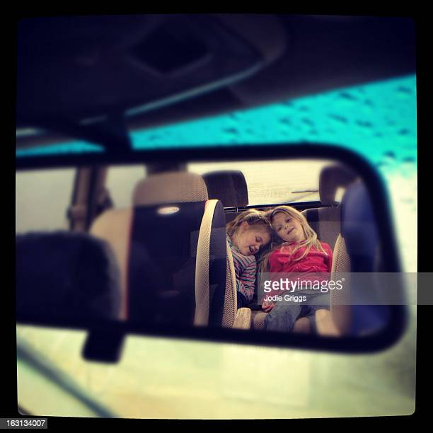Looking at two children in a car rear view mirror